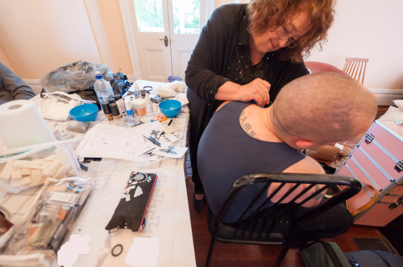 makeup artist painting tattoo on mans neck standing near table with makeup tools and products